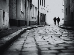 walking down the street (Sandy...J) Tags: olympus walking monochrom blackwhite bw people urban street streetphotography atmosphere light cobblestones city horsten