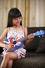 Playing guitar (Patrick Foto ;)) Tags: school portrait people music playing cute home girl face smiling female asian fun thailand happy person one kid student education alone sitting child looking ukulele little guitar song room joy daughter adorable lifestyle indoor sofa single thai instrument practice concept schoolgirl enjoying elementary caucasian