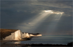 Heavenly Spotlights on the Sisters (adrians_art) Tags: uk blue light red sea england sky white storm black beach water weather yellow clouds reflections dark landscape coast chalk waves mood unitedkingdom atmosphere stormy cliffs shore rays sevensisters eastsussex beams englishchannel