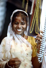22-822 (ndpa / s. lundeen, archivist) Tags: city woman india color film smile face smiling shop 35mm 22 necklace beads store clothing candid indian nick citylife streetphotography streetlife jewelry ring clothes bracelet varanasi 1970s kashi youngwoman allrightsreserved bindi necklaces unidentified banaras benares dewolf reddot piercednose uttarpradesh northernindia nickdewolf photographbynickdewolf foreheaddot reel22 dotonherforehead thenickdewolffoundation imageuserequestsarewelcomeviaflickrmailornickdewolfphotoarchiveatgmaildotcom