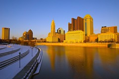 Golden Skyline_Columbus (Sneezzzzz) Tags: city winter sunset ohio snow reflection building skyline architecture river unitedstates 5photosaday columbusdowntown sonyslt pwwinter