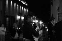 strumming.. (camelot98.) Tags: street leica city bw monochrome musicians night contrast mexico lights mono blackwhite noir dof bokeh guitar grain streetphotography guanajuato mexicans summilux mariachis
