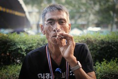Krung Thep, the city of angels (slow paths images) Tags: street travel portrait man face pose asian thailand asia southeastasia bangkok cigarette smoke politics smoking demonstration thai gaze protester krungthep thecityofangels fredcan antigovernmentmarch