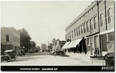 Business Street, Converse, Indiana (Hoosier Recollections) Tags: people usa signs man men history cars buildings advertising awning clothing cafe garage hats restaurants indiana streetscene converse transportation shops pedestrians trucks storefronts automobiles banks businesses barbers miamicounty realphoto hoosierrecollections