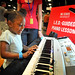 A little girl learns to play the piano by following LED lights on a keyboard at an NC State booth at Maker Faire.