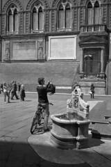 Bike, smartphone and fountain (Franco & Lia) Tags: street blackandwhite film analog noiretblanc bologna apx100 epson agfa biancoenero argentique piazzamaggiore pellicola analogico v500 nikonl35af2 l35af2