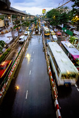 From the archives: Bangkok traffic in the rain (angeloangelo) Tags: road street city travel urban storm reflection bus cars film wet rain clouds thailand lights movement construction asia southeastasia traffic angle bangkok monsoon transportation 20mm lightrail birdseye canonef20mmf28usm
