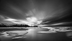 In The Beginning MC (Mabry Campbell) Tags: longexposure sunset blackandwhite bw mountain snow seascape mountains reflection ice water monochrome berg canon landscape photography coast photo iceland europe photographer image fav50 lagoon fav20 coastal photograph le april 100 scandinavia campbell