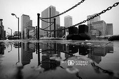 London Unchained (david gutierrez [ www.davidgutierrez.co.uk ]) Tags: city uk winter urban blackandwhite bw cold reflection london art water monochrome rain skyline architecture skyscraper buildings photography cityscape perspective structure architectural chain docklands cityoflondon lowview davidgutierrez pentaxk5