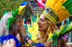 Makeup adjustment (elizunseelie) Tags: city portrait people woman west smile yellow festival gold scotland costume women samba dancers faces glasgow candid group feathers scottish parade end jewels performer gems headdress