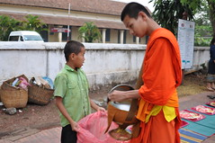 The monks do their bit of charity as well (oldandsolo) Tags: southeastasia earlymorning buddhism tourists lp laos luangprabang buddhistmonk laopdr makingmerit unescoworldheritagecity buddhistreligion takbat buddhistfaith morningalmsgivingritualluangprabang morningalmsgivinginluangprabang