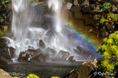 Rainbow at the end of the waterfall with colomn basalt rocks