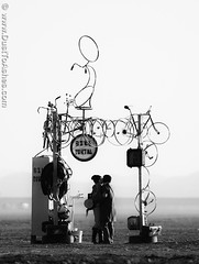 Burning Man 2014 - Lovers (Dust To Ashes) Tags: girls people sculpture man art bike bicycle women kiss kissing couple burningman blackrockcity burning ashes installation portal dust johnnie gerlach 2014 nevadadesert olivan caravansary burningmanart burningmanfestival dusttoashes bm2014 wwwdusttoashescom burningman2014