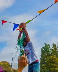 At the Tipping Point (Steve Taylor (Photography)) Tags: colourful green fun liquid man newzealand nz southisland canterbury christchurch city wet sky cloud 221gloucesterstreet colours festival holi holifestival tshirt pot tipping bunting soaked