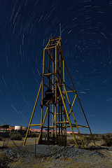 north star headframe. mojave desert, ca. 2016. (eyetwist) Tags: eyetwistkevinballuff eyetwist night abandoned headframe mine ruins gold mining urbex mojavedesert nikon nikond7000 d7000 nikkor capturenx2 1024mmf3545g fullmoon photography desert arid dark longexposure moonlight moonlit gel npy nocturne highdesert mojave california long exposure wideangle stars startrails northstar polaris spin light painting lightpainting forgotten ruin decay architecture faded weathered exploring saturated yellow industry industrial rock wreckage tailings rocks tungsten mineshaft structure infrastructure spinning trails headlights