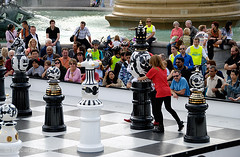 Woman moving a giant chess piece during a game in Trafalgar Square, London, England. The Tournament, an installation created by Spanish designer, Jaime Hayón consists of a gigantic chess set, with 2m high ceramic pieces designed by Hayón on a specially cr (Roberto Herrett) Tags: uk england people woman game london english horizontal set giant women pieces board chess trafalgarsquare tournament installation british spectators popular 2009 stockphoto londondesignfestival jaimehayón rherrettflk chessfederation