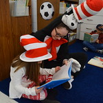 Student in Cat in the Hat costume helps elementary student read a book