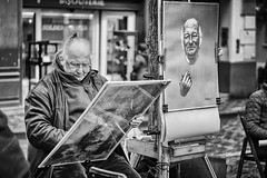 The Painter who Drew Himself. (PabloLopezPhotography.com) Tags: street artist paris montmartre france europe pablo lopez pablolopez placedutertre place tertre district easel tourist reminder time mecca modern art blackandwhite black white century penniless portraitist exhibit sell painting paintings city issue space man baseball cap old brush photography streetphotography candid scene