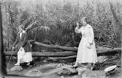 Two unidentified women, whole-length, wearing ankle length skirts and walking shoes, crossing a stream, one with the help of a stick, Mount Buffalo, Vic. (State Library Victoria Collections) Tags: 1920s trek walking 1930s hiking walk hike bushwalking 1910s 1890s early1900s statelibraryofvictoria