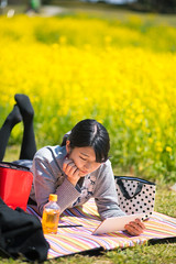 Young woman relaxing on picnic blanket (Apricot Cafe) Tags: img24639 2024years asia asianandindianethnicities canonef85mmf18usm japan japaneseethnicity tokyojapan tokyobay bag blanket casualclothing charming cheerful citylife copyspace day digitaltablet enjoyment freedom friendship fulllength grass happiness indoors leisureactivity lifestyles looking lyingdown meadow mustardplant oneperson onlywomen outdoors petbottle photography picnic publicpark relaxation relaxing smiling springtime tea vertical weekendactivities women youngadult