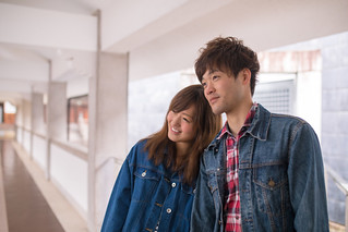 Happy young couple leaning each other in white corridor