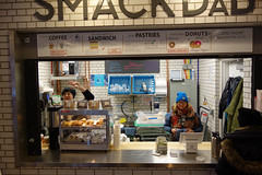 cold morning, hot coffee (KevinIrvineChi) Tags: smackdabchi smack dab chicago chicagoist chilly chicagotransit cta ctabrownline rail station train lakeview wellington people cafe togo go grab grabgo grabngo donuts doughnuts coffee halfwit tins muffins biscuits breakfast morning commuters scarf blue hat rainbow sony dscrx100 waving case display sandwich pastries cups sink stainless steel