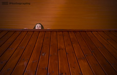 Peek-a-boo (C.M_Photography) Tags: child girl peeaboo wood church interior panel knots varnish brown young funny sad lines sonya7r2 sonyfe28mm