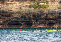 Kayakers paddling along the Sea Caves at the Pictured Rocks in Michigan (PhotosToArtByMike) Tags: picturedrocksnationallakeshore kayak kayakers seacave michigan mi picturedrocks upperpeninsulaofmichigan upperpeninsula up sandstonecliffs uppermichigan lakesuperior munising rockycoastline stonybeach beach rockybeach mineralstain mineralstreaks
