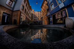 ...NoFishInThisWater... (7H3M4R713N) Tags: fujifilm juliengrosjean switzerland swiss placecoquillon fountain fontaine water reflexion manualfocus manuallens rokinon8mmf28 8mm fisheye wideangle streetphotographie street colorfull color morninglight xt2