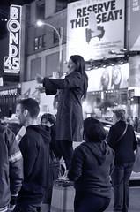 Happy tourist standing on streetlight base. (sjnnyny) Tags: city newyork night manhattan tourists timessquare signage theatredistrict bond45 pentaxk5iis sjnnyny