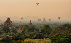 Dawn over Bagan (Aubrey Stoll) Tags: haze dust balloons morning sunrise landscape stupor buddhism buddha religion historical site trees pasture dry season leaves horizon mountains travel tourism burma myanmar asia south east soft light