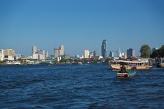 Skyline of Bangkok seen from the busy Chao Phraya river (UweBKK (α 77 on )) Tags: skyline cityscape city urban boats chao phraya river bangkok thailand southeast asia water flow buildings sky blue stream sony alpha 77 slt dslr