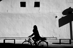 Woman on her bike (Chranton) Tags: life street trip travel light shadow vacation portrait people blackandwhite bw woman sunlight abstract black france art girl monochrome strange lines bicycle silhouette 35mm dark french fun photography photo eyes europe fuji cyclist shadows yeah lyon shots framed district extreme great existentialism young streetphotography silhouettes free style monochromatic stranger x wanderlust artsy human photographs national photograph journey cycle fujifilm eurotrip monochrom luxury ff carefree bnw humans harsh reportage existential x100 fujix100s x100s fujifilmx100s