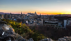 Dusk by the Rock (NathanJNixon) Tags: edinburgh scotland europe united kingdom land city cityscape downtown cityline sky skyline clouds cloud cloudy blue yellow orange red black bright light sunset dusk sun clock clocktower history old histroic historic flowers bush rock rocky cliff hill hillside overlook landscape highlight tower roof buildings building travel magic beauty beautiful calm peace color colorful life calming evening afternoon winter spring scottish british composition canon dslr 60d eos lens nature natural