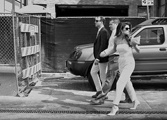 Holds A Grudge (burnt dirt) Tags: houston texas downtown town city mainstreet street sidewalk streetphotography fujifilm xt1 bw blackandwhite girl woman people person bag purse phone cellphone man men crowd group heels stilettos lookbackwards blonde pantsuit glasses sunglasses curls walking mad angry holdinghands nothappy annoyed