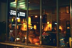 Through a pub window from the sidewalk near the railway station in King street Newtown NSW at night - Autumn 2017 (fantasma A slide) (nicephotog) Tags: newtown night king street rain sidewalk people customers pub drinking social window lounge sydney nsw alchohol public nightonearth fantasma ghost