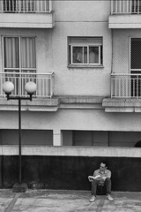 the reader (ɐunןuospıʌɐp) Tags: ifttt 500px city people street window bw house outdoor architecture building black white adult man lifestyle monochrome home reading book one outdoors