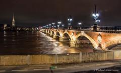 The Pont de Pierre in Bordeaux at Night (Michael Guttman) Tags: pontdepierre stonebridge garonne bordeaux france bridge river night nightshot archedbridge basiliquesaintmicheldebordeaux belltower cathedral nightlights
