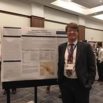 A history major presents his research during a poster presentation.
