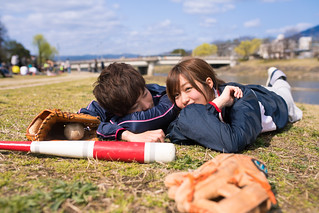 Young athlete couple lying on grass together after playing baseball