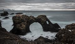 Arnarstapi arch - Iceland (jerry_lake) Tags: 41seconds 7thmarch2017cama arnarstapi atlanticocean fotobuzz iso50 iceland iceland2017 le nikon1424mmf28 arch coastline f90 mountains sea seabirds snow