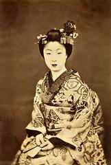 A Kyō-Maiko in Ceremonial Dress 1880s (Blue Ruin 1) Tags: maiko apprenticegeisha kyomaiko kyotoapprentice geiko geisha kanzashi haneri ceremonialkimono japanese japan meijiperiod 1880s albumenphotograph sepia sensu foldingfan