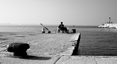 waiting... (Sentieri) Tags: {aggiungereleparolechiavedelimitatedapuntoevirgola} waiting fish fisherman fishing sea sky bw bianco e nero pescatore pesce attesa scogli rocks boat sailing harbour faro people nikon d700 sigma 50mm italy sunset adriatico adriatic rimini emiliaromagna blackwhite