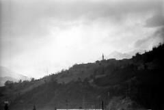 04a3171 13 (ndpa / s. lundeen, archivist) Tags: nick dewolf nickdewolf bw blackwhite photographbynickdewolf film monochrome blackandwhite april 1971 1970s 35mm europe centraleurope austria austrian switzerland swiss alpine alps roadtrip ontheroad mountains building church steeple hillside landscape graubünden grisons tower