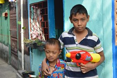 boy holding water gun and maybe a hostage (the foreign photographer - ฝรั่งถ่) Tags: boy squirt water gun brother khlong thanon portraits bangkhen bangkok thailand nikon d3200 songkran thai new year