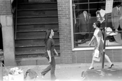 h3-68 06 (ndpa / s. lundeen, archivist) Tags: nick dewolf nickdewolf bw blackwhite photographbynickdewolf film monochrome blackandwhite city summer 1968 1960s 35mm boston massachusetts candid streetphotography citylife streetlife people youngpeople beaconhill charlesstreet sidewalk pedestrians store shop business window windows storewindow simonsons clothingstore street car vehicle automobile parkedcar stairs stairway woman women youngwoman youngwomen glasses sign menssuits tailor tailors cleansers