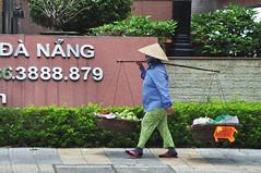 Life balance (Roving I) Tags: vendors vietnam signs street balance conicalhats workingwomen walking loads technologycentres danang