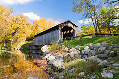 Fallasburg Covered Bridge, Lowell Michigan, USA (Craig - S) Tags: park old travel bridge blue autumn sky orange usa white color reflection fall tourism water grass leaves yellow horizontal clouds rural creek vintage river woods rocks stream pretty crystal stones michigan rustic vivid floating peaceful historic changing covered coveredbridge serene railing puffy pure woodenbridge tranquil woodbridge lowell kentcounty fallasburg vergennestownship flatriver browntruss fallasburghistoricaldistrict