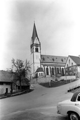04a3671 24 (ndpa / s. lundeen, archivist) Tags: nick dewolf nickdewolf bw blackwhite photographbynickdewolf film monochrome blackandwhite april 1971 1970s 35mm europe centraleurope switzerland swiss suisse schweitz ontheroad roadtrip town village unidentified building architecture church steeple tower street road buildings car vehicle automobile streetsign schlossstrasse people benches parkbenches seated sitting clock clocktower