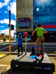 Helmet Optional (Steve Taylor (Photography)) Tags: superstreetarcade videogame gameboy helmet vertigotech gapfiller jump joystick buttons screen vodafone monsvision jumping cartridge bicycleclips tuam high street attackofthecones cone trafficlights corner building office window road colourful fun girl man child newzealand nz southisland canterbury christchurch cbd city lensflare sunny sunshine 248tuamstreet